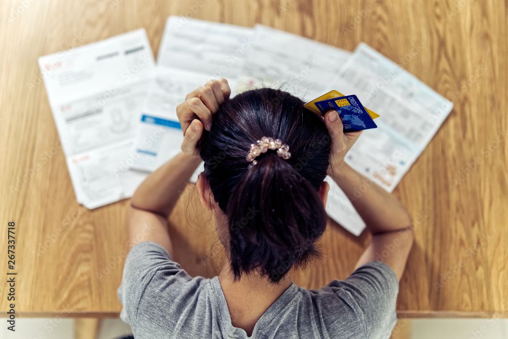 Fototapety, obrazy: Top view of stressed young sitting Asian woman hands holding the head worry about find money to pay credit card debt and all loan bills. Financial problem concept.