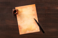 A Vintage Background With A Nib Pen On Old Paper, With An Ink Well, Shot From The Top On A Dark Wooden Background With Copy Space
