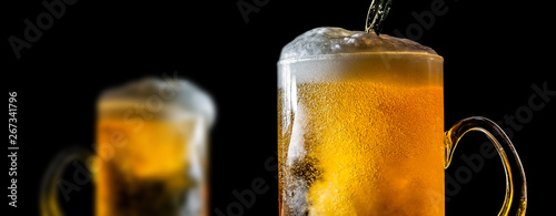 Fotografia  Two large glasses of beer with foam close-up, facing each other, isolated against a black background
