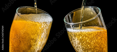 Fototapeta Two large glasses of beer with foam close-up, facing each other, isolated against a black background. Two overflowing glasses of beer with flowing foam. obraz