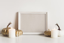 Composition With Photo Frame, White Pumpkins And Candles. Mockup Copy Space For Artwork