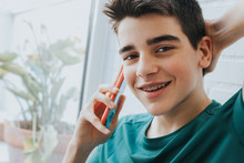 Portrait Of A Male Teenager With Braces And Mobile Phone