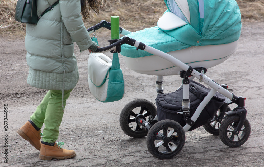 Fototapety, obrazy: Girl with a stroller goes on the road in winter