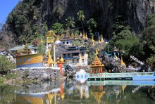 View On Colorful Kitschy Temple With Golden Towers Reflecting In A Lake Against Steep Mountain Face And Bridge - Bayin Nyi Begyinni Pagoda Near Hpa An, Myanmar