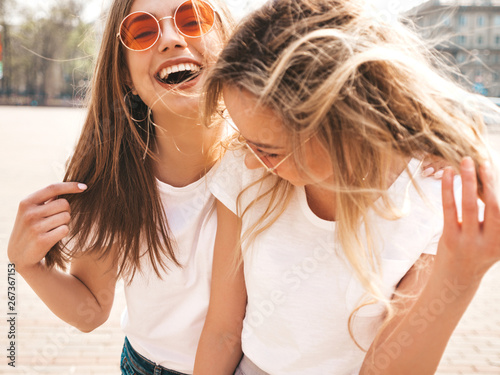 Fotografia  Portrait of two young beautiful blond smiling hipster girls in trendy summer white t-shirt clothes