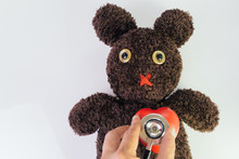 Doctor's Hand Holding Stethoscope Put On Red Heart On Cute Brown Handmade Fluffy Doll With Pitty Eyes, Healthcare For Children Or Kids, Medical Learning Class