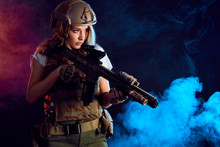 Female Storm Trooper In Military Camouflage Uniform Protected With Helmet, Body Armour With Submachine Gun Seeking Aims In The Smoky Darkness