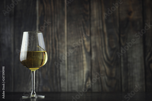 Fototapeta Transparent bottle of white dry wine on the table. White wine glass on a wooden background. obraz