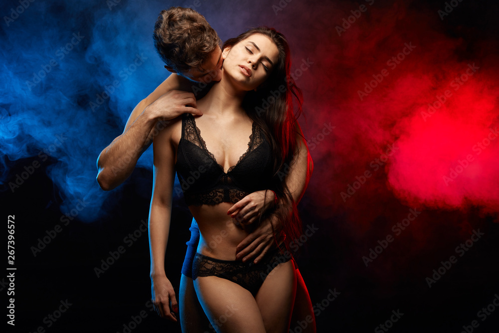 Fototapety, obrazy: emotional beautiful fit woman enjoying her man's kisses. isolated black background.sexual attraction