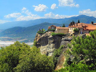 Fototapeta na wymiar Monastery Meteora Greece. View at mountains, green forest and blue sky with clouds. Monastery Holy Trinity. Meteora rocks