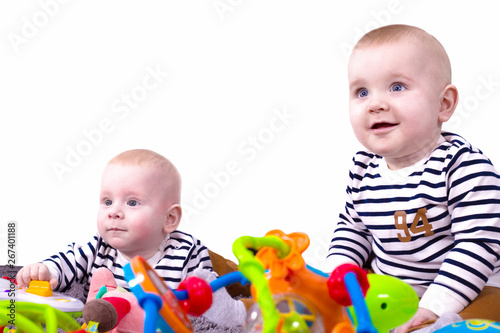 Fényképezés  Adorable non-identical twins, also known as fraternal twins or dizygotic twins play with toys isolated on white background
