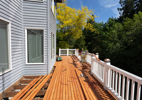 Fototapeta Outdoor red wooden cedar deck being remodeled with new floor boards freshly installed obraz