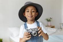 Art, Technology, Hobby And Childhood Concept. Handsome Joyful Dark Skinned Black Schoolboy Interested In Photography, Holding Vintage Film Camera, Smiling, Wearing Elegant Round Hat In Bedroom