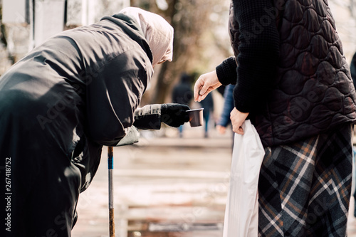 Photo of passerby givining alms for old hungry homeless female beggar on street Canvas Print