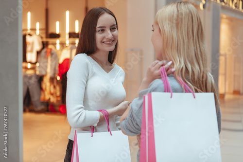 Fotomural  Gorgeous happy woman talking to her friend, standing at the shopping mall