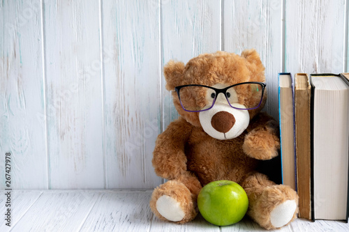 Fényképezés  Photo of a stack of books with a bear, an apple and a place for an inscription on a wooden background