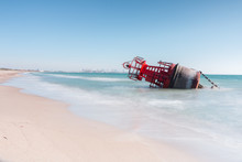 A Navigation Buoy Stranded On The Beach By The Strong Currents Of A Storm With A Long Exposition For A Silk Effect