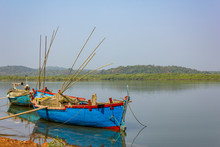 Two Large Old Fishing Boats With Motors And Fishing Rods Anchored Off The Coast Against The Backdrop Of A River And Green Forest