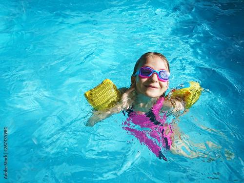 dziewczynka pływająca w basenie - fototapety na wymiar