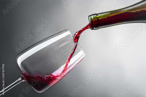 Photo  Red wine being poured into wineglass.