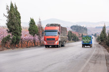 Red Truck And Tractor Driving On The Country Road In China.