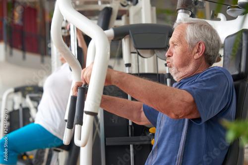 Foto  Elderly man doing press push weight exercise
