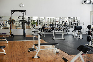 Fototapeta na wymiar Gym interior with equipment. Modern fitness center with training equipment. Commercial gym interior design.