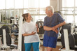 Two happpy senior people at gym. Joyful elderly couple laughing after a sport workout at fitness club. People, sport, training, positive facial expressions.
