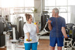 Happy senior couple training with dumbbells in gym. Smiling elderly people exercising at fitness center. Sport, relationship, healthy lifestyle concept.