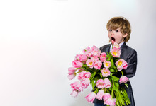 Gift To Mum. Surprised Little Boy With Bouquet Of Tulips. On March 8, International Women's Day, Mother's Day, Valentines Day. Wedding Concept. Stylish Little Boy In Elegant Suit Holds Bouquet Tulips.