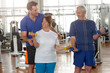 Handsome male trainer instructing senior woman in gym. Elderly people working out at fitness club. Sport, recreation, healthy lifestyle.