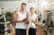 Young athletic couple at fitness club. Young fit man and woman looking at camera at gym. Woman showing thumb up sign.