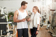 Man and woman looking at each other in gym. Athletic man holding digital tablet and looking at woman. People, sport, relationship and wellness concept.