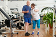 Mature couple gesturing thumbs up at gym. Portrait of happy senior people showing thumbs up at fitness club. People, sport, fitness and gestures concept.