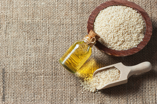 Photo Glass bottle of sesame oil and raw sesame seeds in wooden shovel and bowl on burlap sack