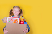 Blond Little Girl Holding A Box With Toys On Yellow Background. Donation Concept..