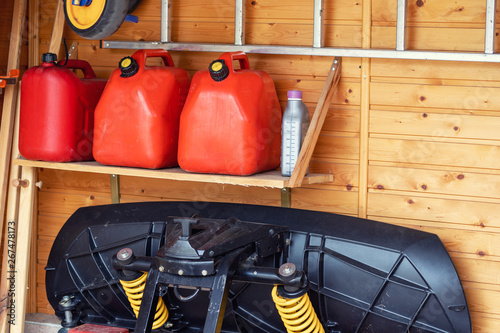Obraz na plátně Garage corner with three red plastic fuel cans , staircase and snow plough for atv with wooden wall on background