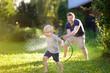Leinwandbild Motiv Funny little boy with his father playing with garden hose in sunny backyard. Preschooler child having fun with spray of water.