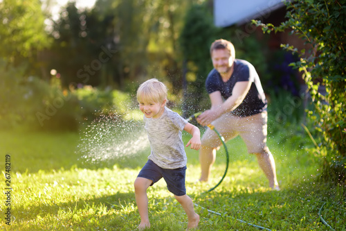 Fototapeta Funny little boy with his father playing with garden hose in sunny backyard. Preschooler child having fun with spray of water. obraz