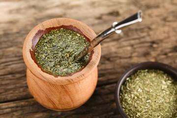 Frisch aufgegossener Mate-Tee in Holztasse mit Bombilla (Metalltrinkrohr mit Sieb am Ende), traditionelles lateinamerikanisches Getränk (Selektiver Fokus, Fokus ein Drittel in den Tee)