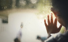 Little Girl  By Window With Raindrops On It On A Rainy Day