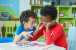 Two boy kid sit on table and coloring in book  in preschool library,Kindergarten school education concept