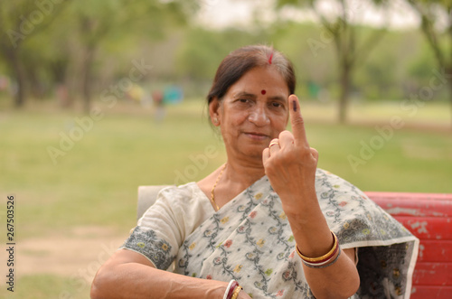 Canvas Prints Monkey A Senior Indian woman citizen sitting on the red bench in a park showing their inked finger after casting their vote in assembly elections in Delhi, India - world's largest democracy. Focus on finger