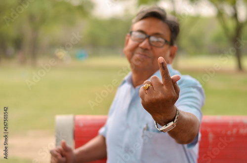 Canvas Prints Monkey Portrait of a Senior Indian retired male sitting on the red bench in a park and showing his inked finger after casting their vote in Indian assembly elections
