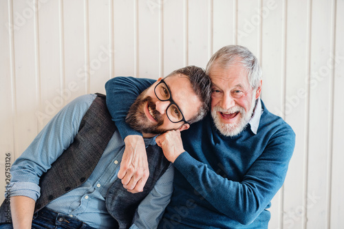 Fotografie, Obraz  A portrait of adult hipster son and senior father sitting on floor indoors at home