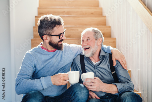 Fotografiet  An adult hipster son and senior father sitting on stairs indoors at home, talking