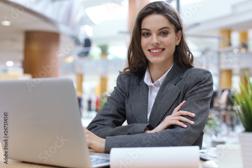 Fotografía  Portrait of a cheerful young businesswoman sitting at the table in office and looking at camera