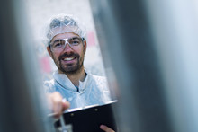 Portrait Of Smiling Technologist Holding Checklist And Controlling Production In Pharmaceutical Or Chemical Industry.