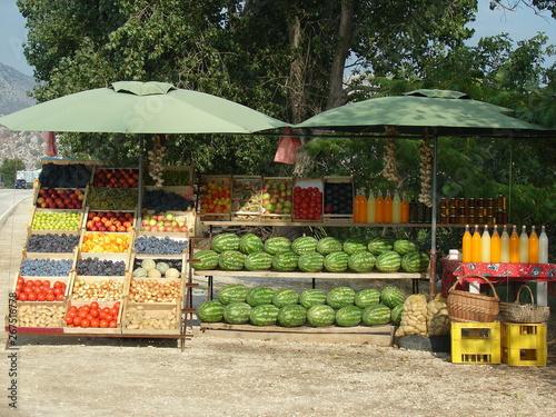 Stargan z owocami i warzywami na sprzedaż, arbuzy, jabłka, śliwki, pomidory, ziemniaki, cytrusy, miód w słoikach i soki domowe w szkalnych butelkach
