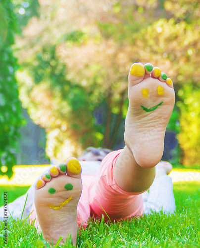 Child lying on green grass Wallpaper Mural